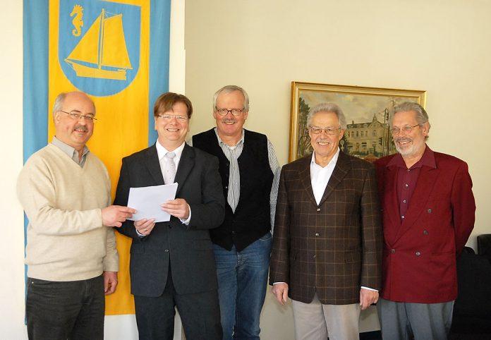 Jens Johannsen gibt seine Bewerbungsunterlagen im Rathaus ab, begleitet von Vertretern der WUB, der FDP und den GRÜNEN