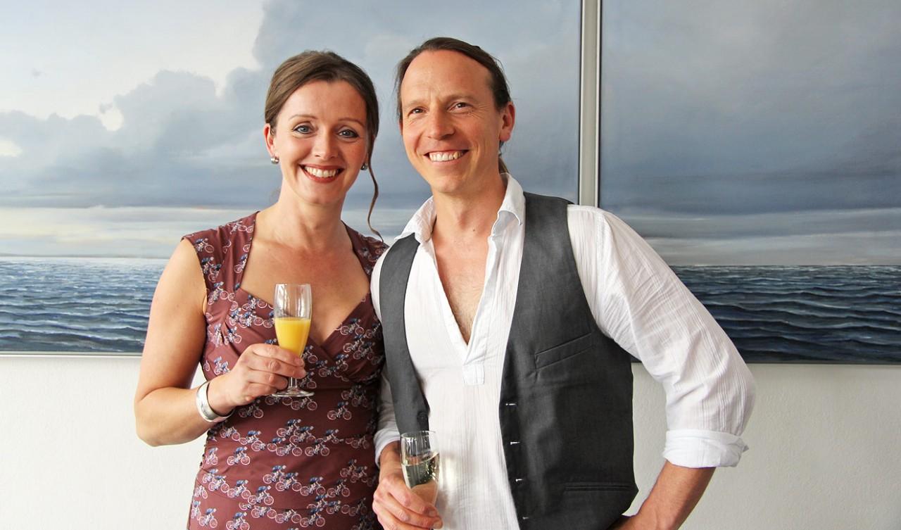 Fröhliche Gastgeber vor dem Meer-Triptychon in der neuen Galerie am Meer: Birgit Brandt und Michael Weigel