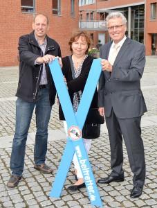 Martin Kauder und Andrea Grose überreichten ein blaues Kreuz an Bürgermeister Volker Owerien (Foto: Kartin Gehrke)