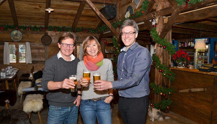 André Rosinski (rechts), Hansjörg Conzelmann und Birte Friedländer stoßen auf die Alpenhütte an. Foto: Katrin Gehrke