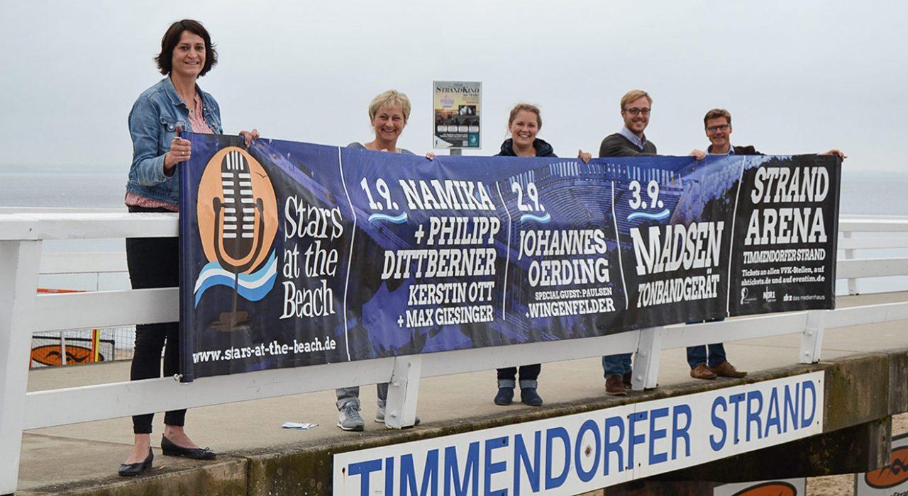 """Die Stars kommen """"at the beach"""": das TSNT-Team mit dem Event-Plakat"""
