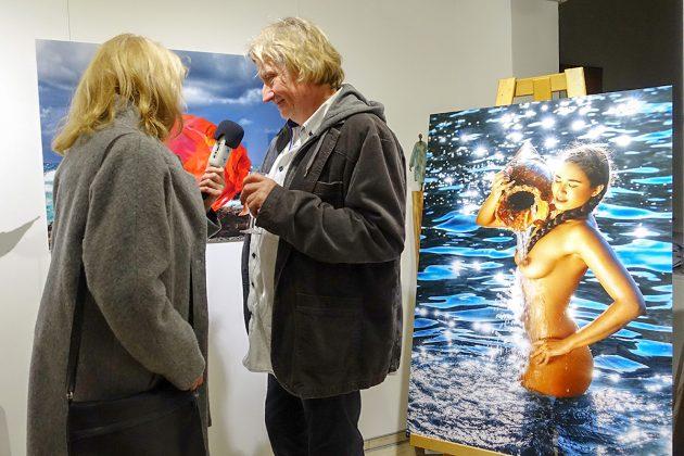 Wim Westfield beim Interview mit einer Reporterin vor einem seiner begehrten Werke mit schönen Frauen mitten im Meer.
