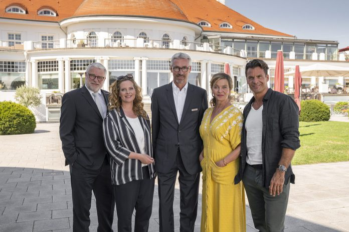 Das Schauspieler-Team gemeinsam mit Hoteldirektor Kay Plesse (Mitte) vor dem stilvollen Gebäude des ATLANTIC Grand Hotel Travemünde