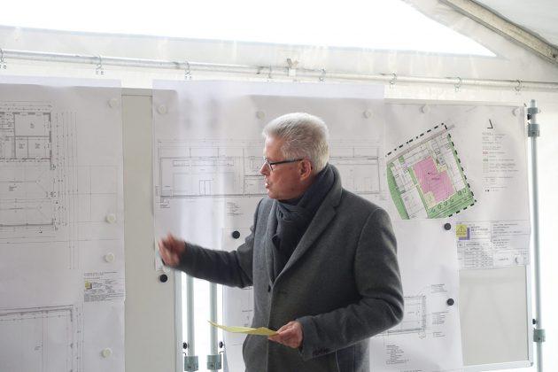 Bürgermeister Volker Owerien erklärt den zahlreichen Zuschauern den Bauplan für das Gemeindehaus in Schürsdorf