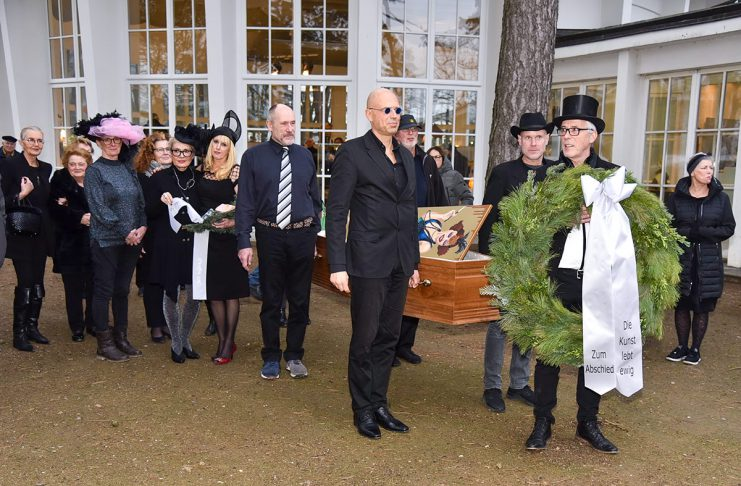 Der Sarg ist gefüllt mit Gemälden, der Kranz wird in Kürze niedergelegt: Trauerfeier für die Kunst vor der Timmendorfer Trinkkurhalle. © Susanne Dittmann