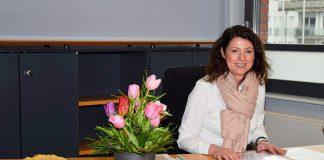 Bürgermeisterin Bettina Schäfer an ihrem Schreibtisch im Bürgerhaus von Scharbeutz. Käsekuchen und Blumen haben ihr die Kollegen zur Begrüßung auf den Schreibtisch gestellt. © Katrin Gehrke
