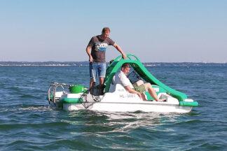 """""""Wir holen den Müll aus dem Meer"""": Schauspieler Fabian Harloff und Strandkorbvermieter Marcus Bade beim Müll-Abfischen mit dem Tretboot."""